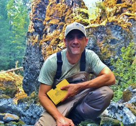 Geoff Hales crouching on a boulder in a forested stream environment holding a field notebook and smiling.