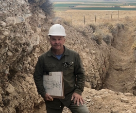 Dr. Hemphill-Haley standing in a paleoseismic trench holding a trench log and smiling